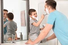 Меньший сын применяясь бреющ пену на сторону папы стоковая фотография rf