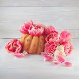 Меньший торт, пирог на деревянной белой плите кухни с весной цветет тюльпаны и розы стоковое фото