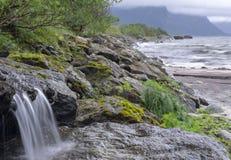 Меньший rill воды брызгая на утесе стоковое изображение