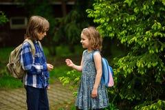 2 меньших студента школы, мальчик и девушка, жизнерадостно связывают на школьном дворе Стоковое Фото