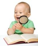 Меньшяя детская игра с книгой и увеличителем стоковое изображение rf