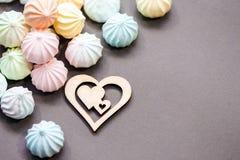 Меренги в пастельных цветах с деревянной диаграммой сердца на серой предпосылке Стоковая Фотография RF