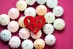 Меренги с деревянной диаграммой сердца на magenta предпосылке Стоковая Фотография