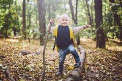 Мероприятия на свежем воздухе темы в природе Смешная маленькая кавказская белокурая девушка идет прогулки в лесе на пересеченной  стоковые фото