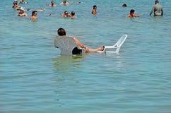 Мертвое море, Израиль - 31-ое мая 2017: люди на стульях ослабляют и плавают в воде мертвого моря в Израиле Туризм стоковое изображение rf