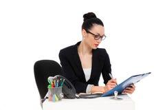 Мерланги коммерсантки на документах, сидя в стуле офиса Стоковое Фото