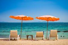 Места зонтика и sunbath пляжа и бортовая таблица на пляже песка Стоковая Фотография RF