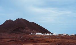 Местная деревня Calhau на ноге вулканического кратера Одиночный Марсианин как сухой красный утес стоит вне от неурожайной пустыни Стоковое Изображение