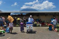 Местная девушка нося мороженое традиционной одежды покупая в уличном рынке в городе Антигуы, в Гватемале, Центральная Америка Стоковые Фотографии RF