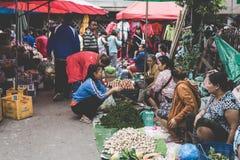 Местная лаосская женщина племени холма продает овощи на ежедневном рынке утра в Luang Prabang, Лаосе 13-ого ноября 2017 Стоковое Изображение