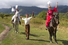 Местные женщины и человек в традиционных одеждах на национальных folkloric играх в Алма-Ате, Казахстане Стоковые Фотографии RF