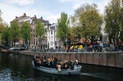 Местные люди и туристы одели в оранжевых одеждах едут на шлюпках и участвуют в праздновать день ` s короля стоковые фото