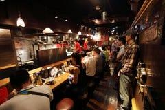 Местные люди смешали при немного туристов dinning рамэны в ресторане Menya Musashi, возможно самый лучший вариант рамэнов в Shinj Стоковые Изображения