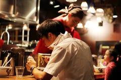 Местные люди смешали при немного туристов dinning рамэны в ресторане Menya Musashi, возможно самый лучший вариант рамэнов в Shinj Стоковое Фото