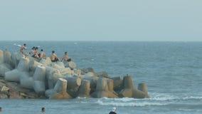 Местные парни сидят на конкретных волнорезах океаном сток-видео