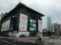 Местный китаец ехал велосипед и прошел Silk торговым центром рынка в пасмурном дне, в Пекине, Китай стоковое фото
