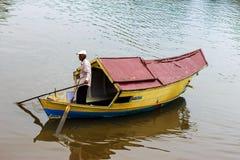 Местный лодочник пересекает реку для того чтобы выбрать вверх клиентов. Стоковые Фотографии RF