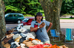 Местный рынок в Уругвае: Уличный торговец продавая тапочки и drin Стоковые Фотографии RF