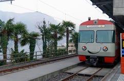 Местный усмехаясь поезд в Лугано, Швейцарии, с пальмами и силуэтами горы Стоковые Фотографии RF