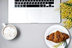 Место для работы женщины с компьтер-книжкой, цветком мимозы, круассаном, кофе a Стоковые Фото