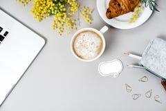 Место для работы женщины с компьтер-книжкой, цветком мимозы, круассаном, кофе a Стоковые Изображения RF