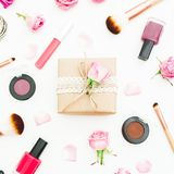 Место для работы женщины с подарочной коробкой, розовыми розами, косметиками, дневником на белой предпосылке Взгляд сверху Плоско Стоковая Фотография RF
