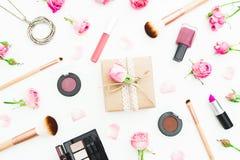 Место для работы женщины с подарочной коробкой, розовыми розами, косметиками, дневником на белой предпосылке Взгляд сверху Плоско Стоковые Изображения RF