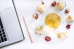 Место для работы на таблице ручки, компьтер-книжки и чашки чаю с сухими розами на таблице работы Взгляд сверху Стоковая Фотография