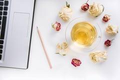Место для работы на таблице ручки, компьтер-книжки и чашки чаю с сухими розами на таблице работы Взгляд сверху Стоковое фото RF