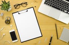 Место для работы стола домашнего офиса с с серебряными аксессуарами тетради, smartphone и офиса на деревянной предпосылке стола Стоковые Изображения RF