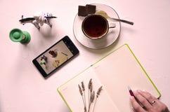 Место для работы с блокнотом, чашкой чаю на белой предпосылке Плоское положение, стол сочинительства стола офиса взгляда сверху Ф стоковое изображение rf