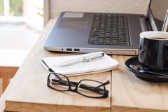 Место для работы с компьтер-книжкой, кофе, тетрадью, и стеклами Стоковое фото RF