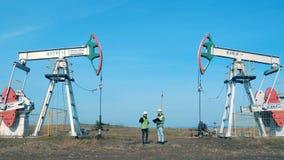 Место извлечения нефти с 2 инженерами связывая между ими Энергия, масло, газ, снаряжение топлива нагнетая сток-видео