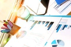 Место службы с компьтер-книжкой, цифровой таблеткой; диаграммы на офисе Стоковые Фото