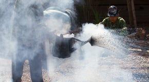 Место строительства дорог при азиатский работник делая асфальт Стоковое Фото