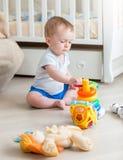 10 месяцев старого мальчика играя с воспитательными игрушками на поле на спальне Стоковое Изображение