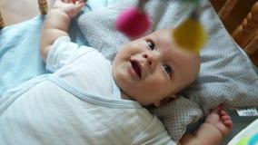 3-месяц-старый младенец лежит в его кровати Ребенок смотрит вверх и усмехается Он active, вытягивая его руки и ноги, раскрывают видеоматериал
