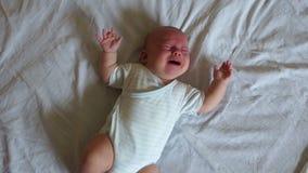 3-месяц-старый ребенок лежит самостоятельно на большой кровати Ребенк screams громко Забота младенца на до год видеоматериал