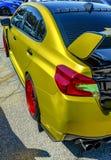 Металлический желтый автомобиль с большим спойлером и красными оправами стоковые фотографии rf