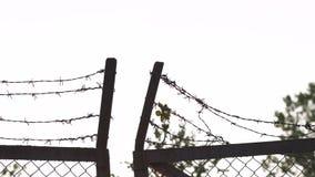 Металл колючей проволоки обнесет забором выравниваясь золотой заход солнца часа - знак клетки опасности и никакой свободы акции видеоматериалы