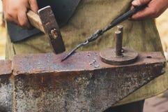 Металл кузнеца работая с молотком на наковальне в кузнице Стоковые Изображения