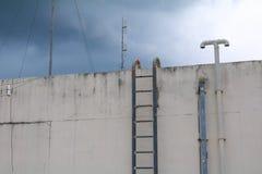 Металл лестницы старый вертикальный промышленный заржавел к цистерне с водой отсутствие рельсов безопасности Стоковые Изображения