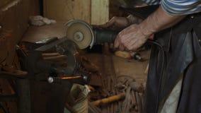 Металл профессионального кузнеца пиля с круглой пилой руки на кузнице сток-видео