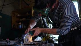 Металл профессионального кузнеца пиля с круглой пилой barehands на кузнице сток-видео