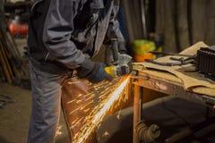 Металл sawing кузнеца с круглой пилой руки стоковая фотография