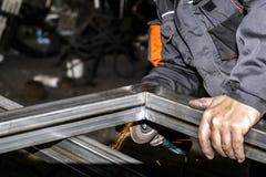 Металл sawing мастера с дисковым шлифовальным станком в мастерской Меля металл с летать искр стоковая фотография