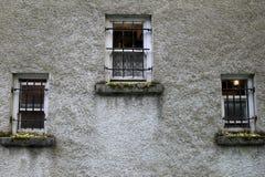 3 металл-запертых окна в каменной стороне жилого дома Стоковые Изображения
