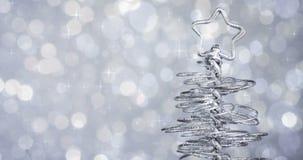 Металлическая современная рождественская елка на серебряной предпосылке bokeh света подкраской сток-видео