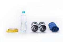 Металлические гантели, бутылка, измеряя лента и полотенце изолированные на белизне Стоковое Изображение RF