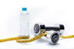 Металлические гантели, бутылка и измеряя лента изолированные на белизне Вода питья Стоковое фото RF